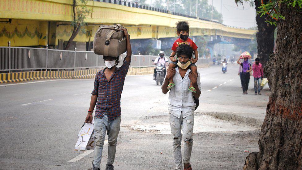 Dois homens caminhando, com mala e crianca