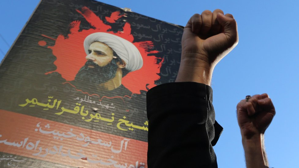 Iranian protesters raise their fists in front of a portrait of Saudi Shia cleric Nimr al-Nimr following execution (3 January 2016)