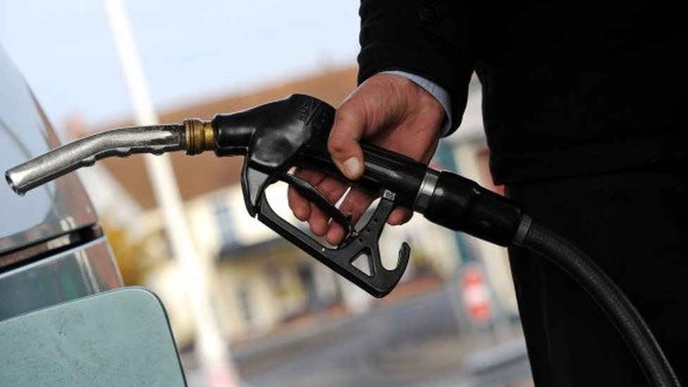 A customer pulls the nozzle of a petrol pump from their car at a petrol station in Egham