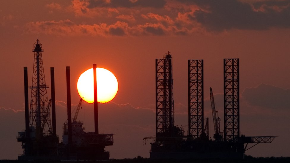 Oil rigs under construction at sunset