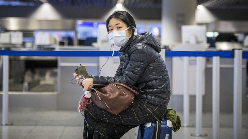 德國法蘭克福機場一位中國女孩在值機櫃台前坐在行李箱上等候(12/3/2021)
