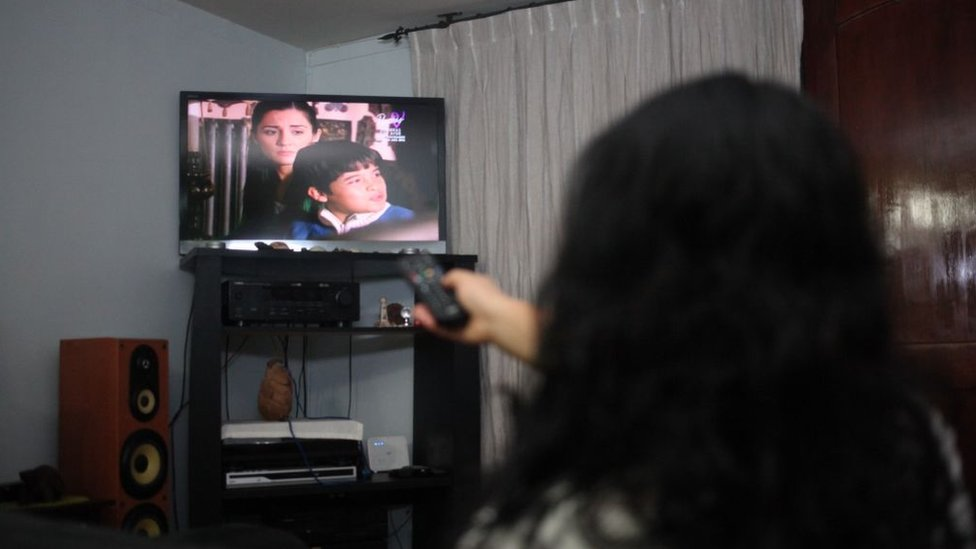 Mujer viendo televisión.