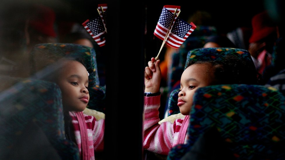 A small black girl waves an American flag, while looking out of the window of a train
