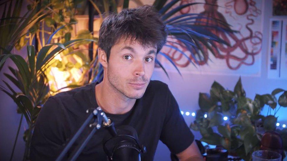 Léo Grasset sentado em uma sala mal iluminada com um microfone à sua frente e vasos de plantas atrás dele. Ele está olhando diretamente para a câmera e com as sobrancelhas erguidas.