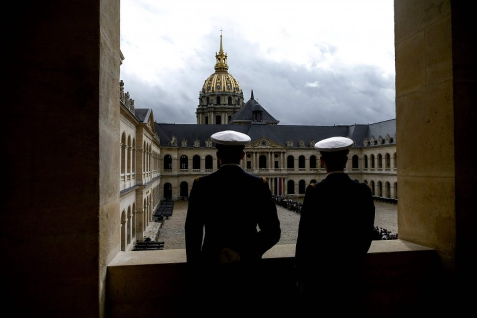 Servicemen look at people queuing to say a final farewell to former French President Jacques Chirac on 29 September 2019.