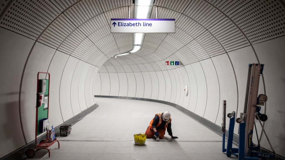A member of the construction team works on the flooring in an access corridor within Liverpool Street Crossrail station