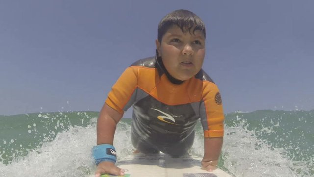 Boy with disabled hand on surfboard