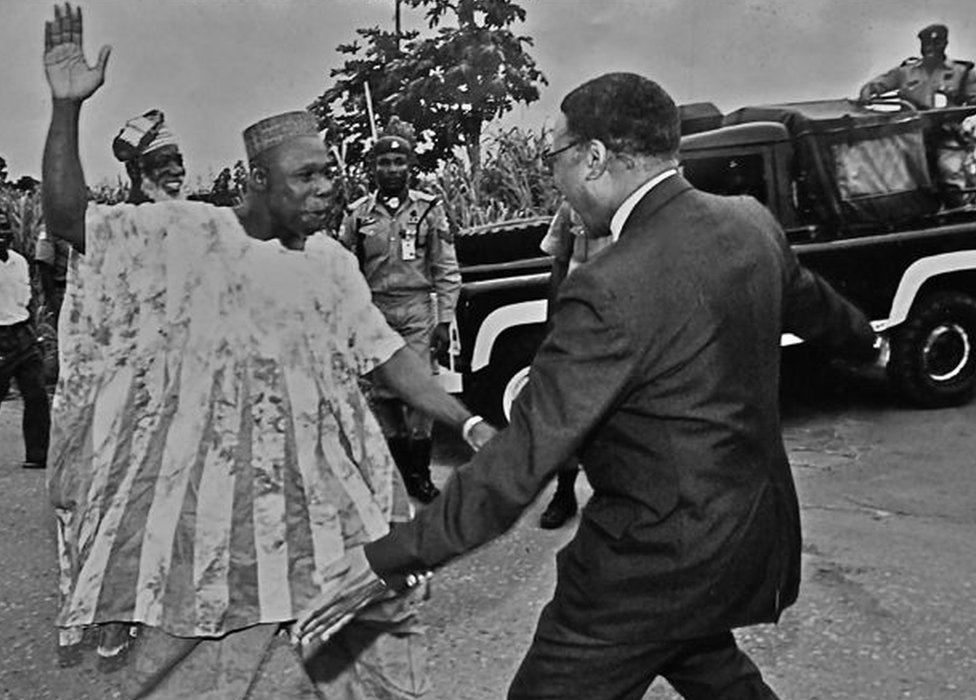 "A photo by Sunmi Smart-Cole entitled: ""How to be a Nigerian"" - 1998, showing former military leader Olusegun Obasanjo (L) pictured a week after he left prison greeting Emeka Anyaoku, then secretary-general of the Commonwealth"