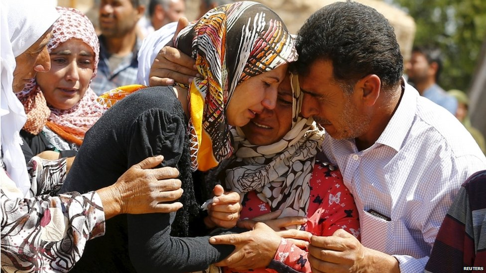 A family mourns for the loss of their relative killed in the Syrian town of Kobani in the border town of Suruc in Sanliurfa province, Turkey, 26 June 2015.