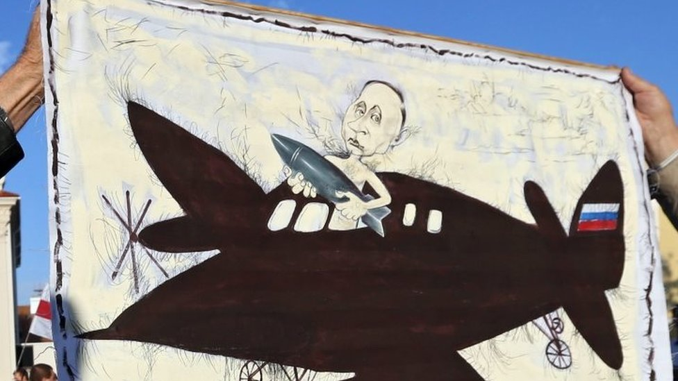 A placard depicting Russian President Vladimir Putin with a bomb on a plane is held by protesters in Minsk. Photo: 4 October 2015