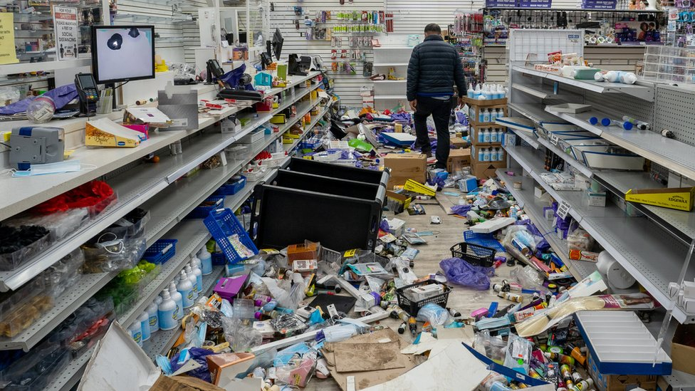 A business owner walks in his looted beauty supply store following protests over the police shooting death of Walter Wallace in Philadelphia