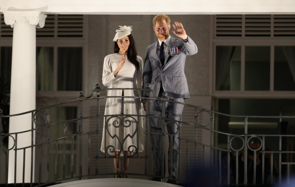 Prince Harry, Duke of Sussex and Meghan, Duchess of Sussex wave from the balcony of the Grand Pacific Hotel in Suva October 23, 2018