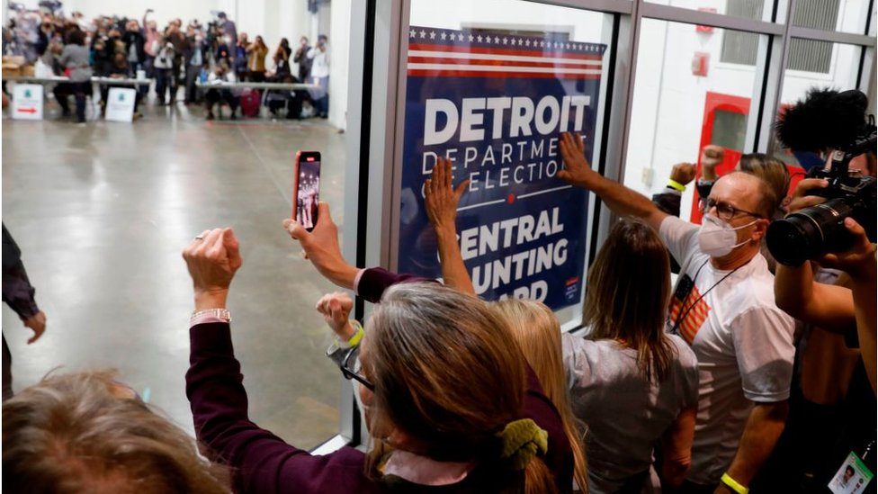 Trump supporters bang on the glass in Michigan where votes are being counted