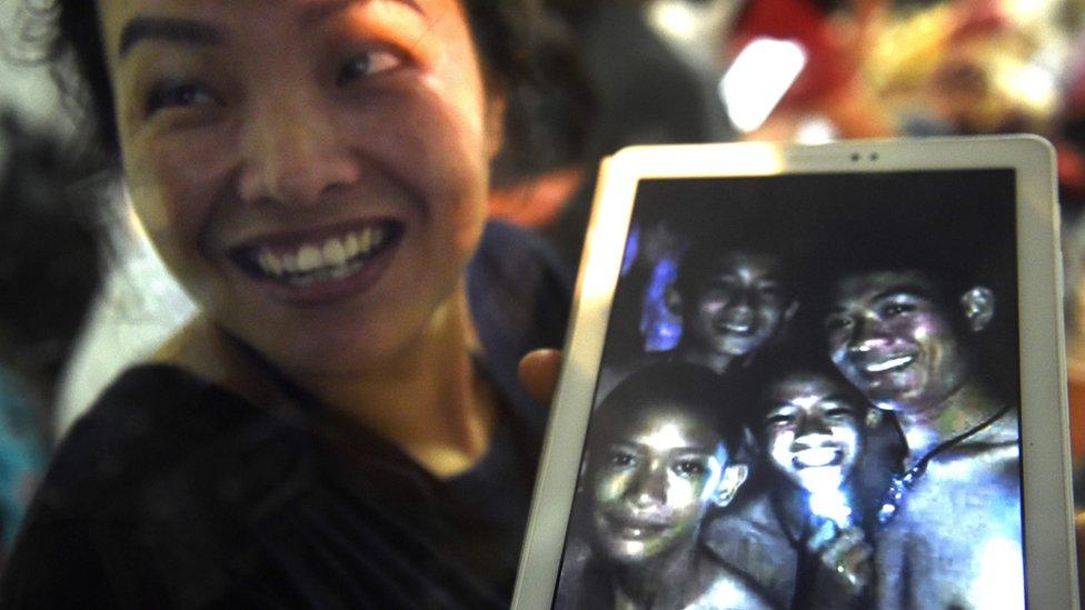 Una madre de los niños muestra una foto de algunos de ellos cuando todavía estaban atrapados.