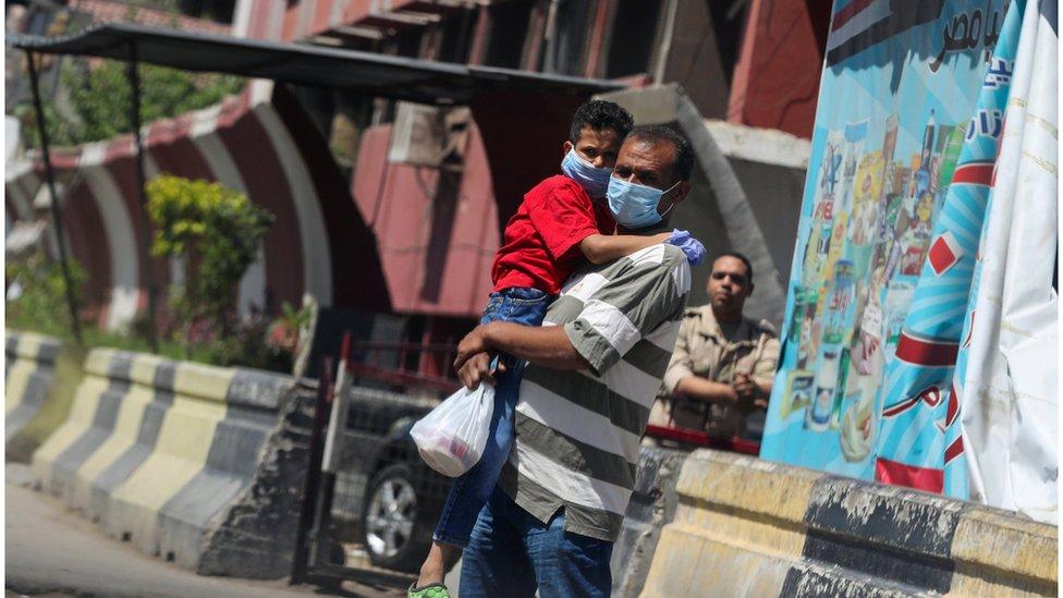 رجل يحمل طفلا وكلاهما يرتدي كمامة
