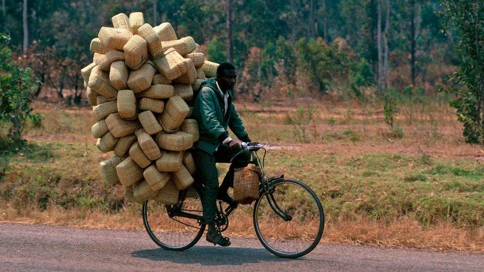 Un hombre en bicicleta en Uganda, cargado de paquetes.
