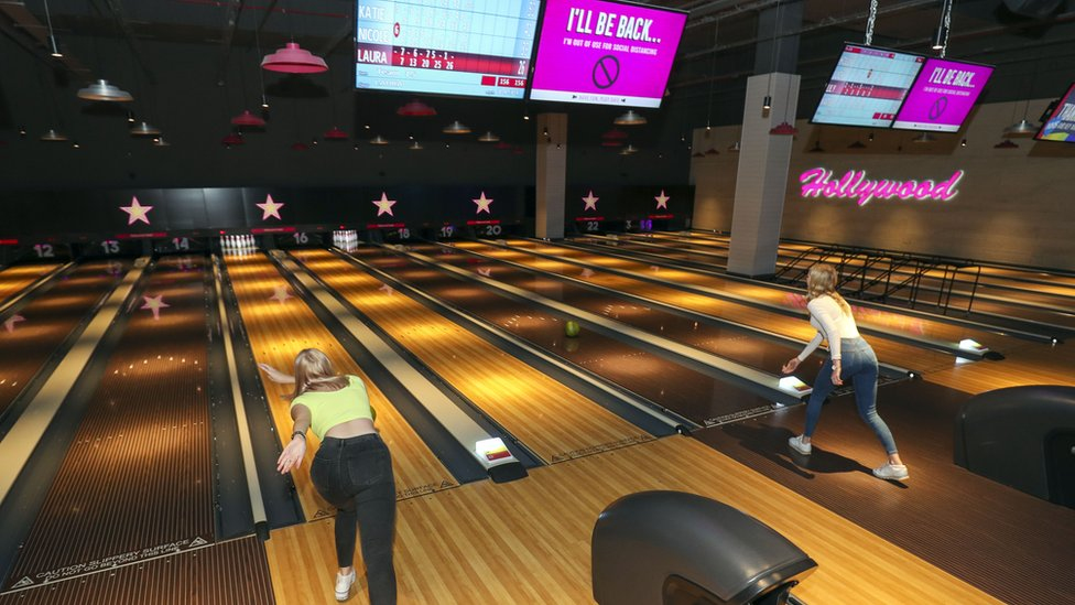 People bowling with empty lanes between them