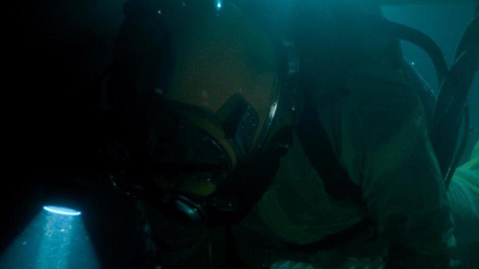 Mergulhador subindo estrutura metálica em cena de documentário