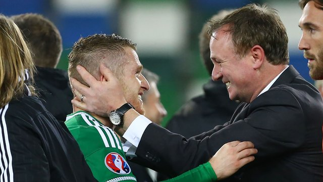 Northern Ireland manager Michael O'Neill embraces skipper Steven Davis after the team's qualification for Euro 2016