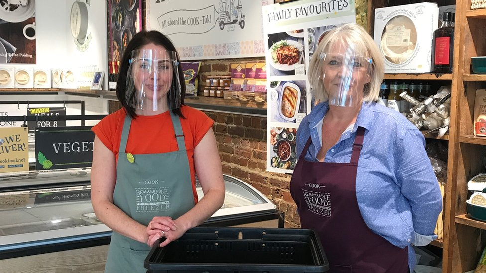 Employees at a Cook Food retail store wearing visors