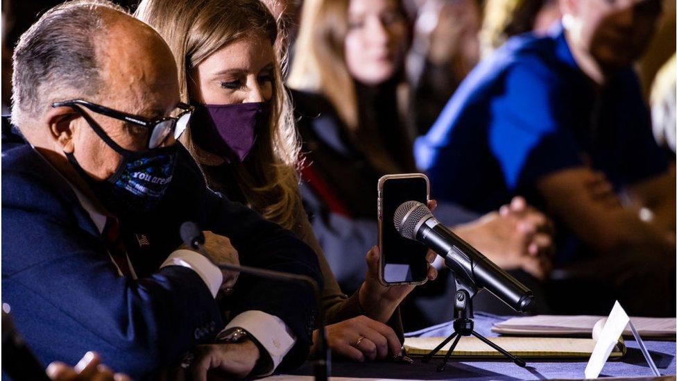 Rudy Giuliani y la abogada Jenna Ellis escuchan al presidente Trump por los parlantes de un teléfono móvil.
