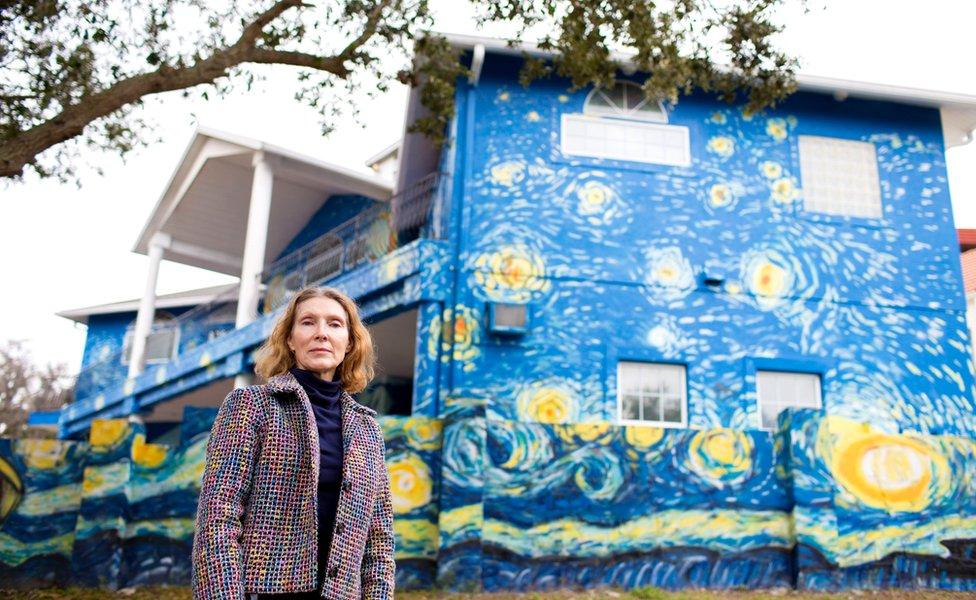 """Nancy Nemhauser afuera de su casa pintada como la """"Noche estrellada"""" de Van Gogh."""