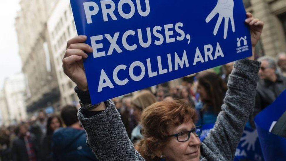 """A woman holds a placard reading """"Enough excuses! Let's welcome now"""" during the Barcelona demonstration (18 February 2017)"""