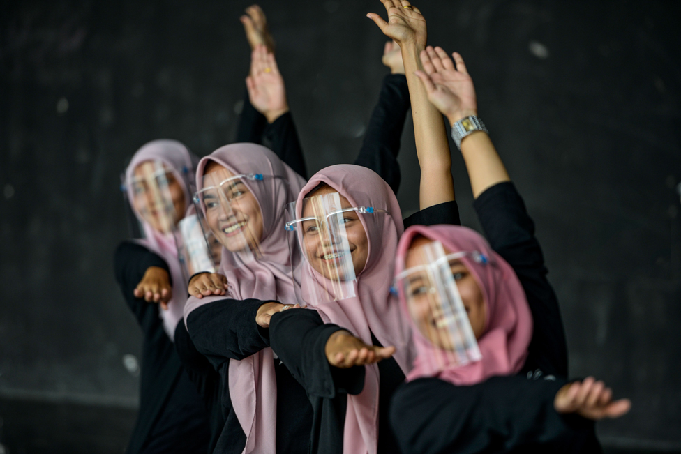 Dancers wearing face shields perform during a rehearsal