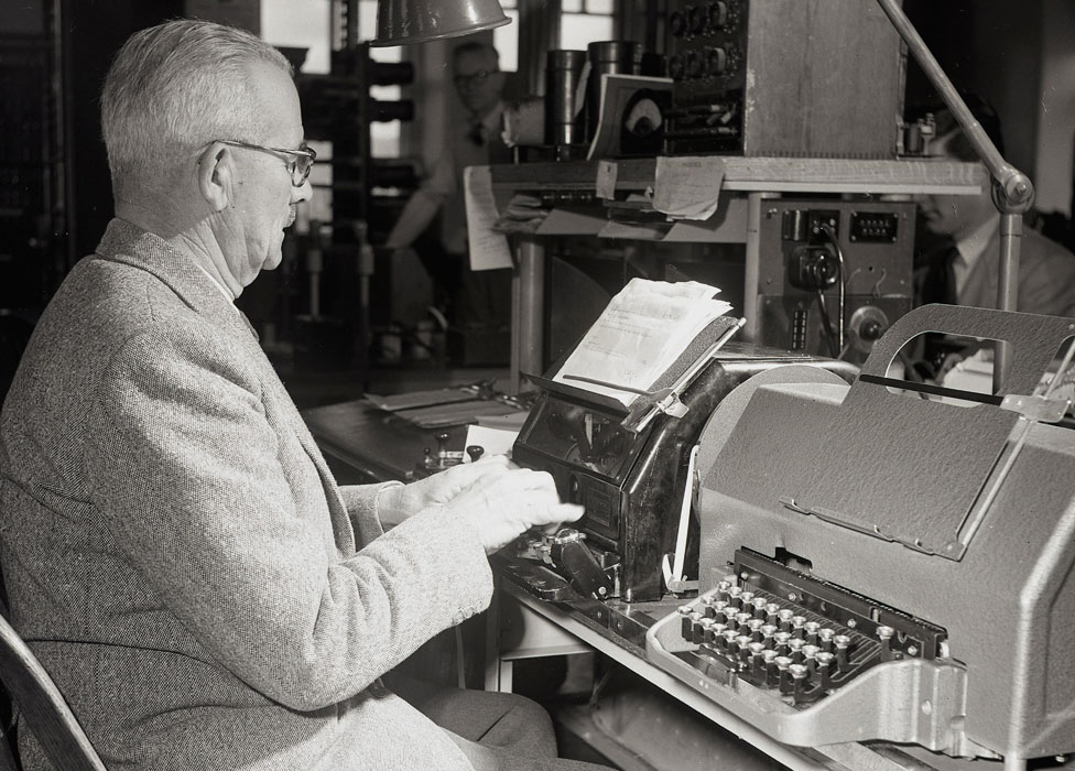 A man sends a telex message in the 1950s