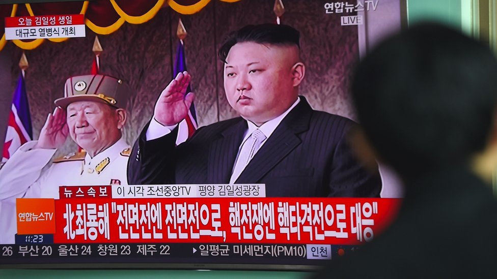 A man watches a television news broadcasting live footage of a military parade in Pyongyang on 15 April.