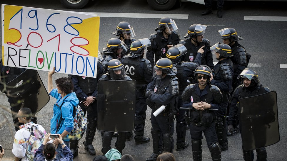 """A man holds a placard reading """"1968-2018 Revolution"""" in front of French CRS riot police at Tolbiac university site, branch of Paris 1 university, 20 April 2018"""