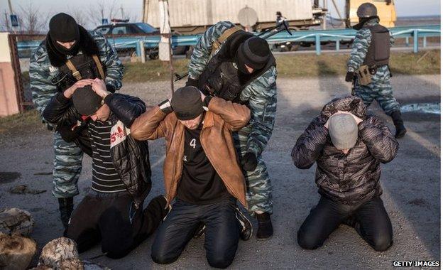 Milicianos pro-rusos revisan a unos transeuntes en un puesto de control en la entrada a la península de Crimea.