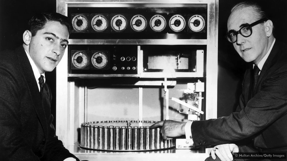 Two men stand next to the Smellovision device
