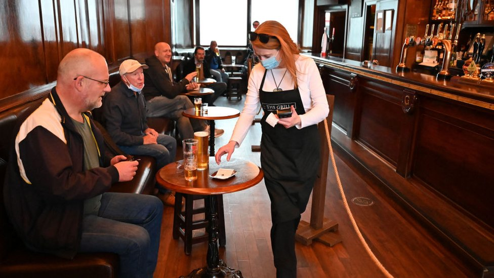 A waitress wears a mask as she works in the pub The Grill in Union Street