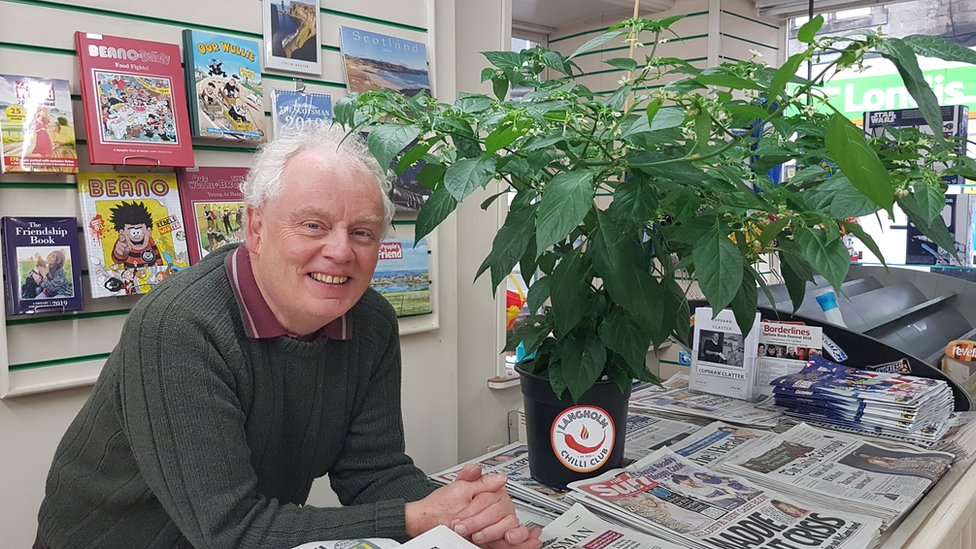 Billy Young and his chilli plant in The Paper Shop in Langholm
