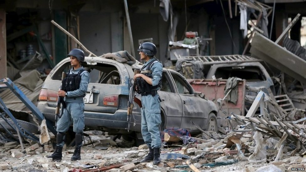Afghan policemen stand guard at the site of a suicide truck bomb in Kabul