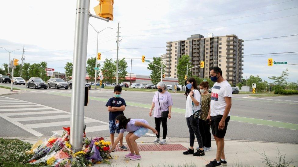 Personas se acercan a dejar flores a un homenaje en plena calle en Ontario, Canadá.