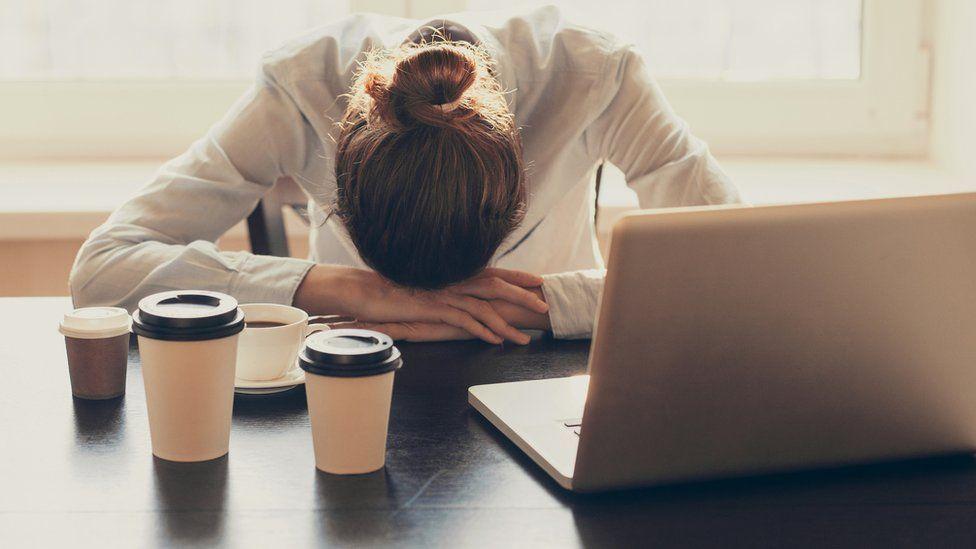 Mujer agotada grente a la computadora