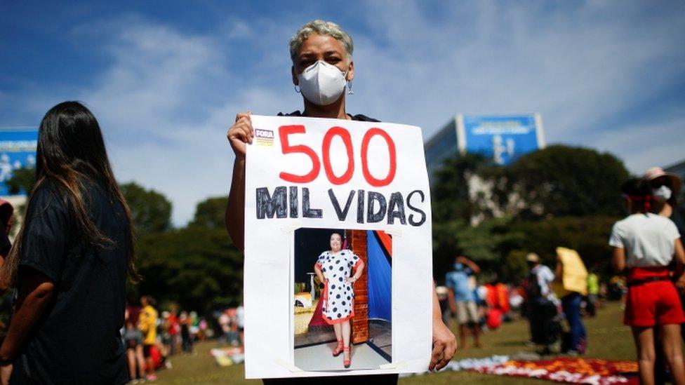 Mulher de máscara segura cartaz que diz '500 mil vidas' e expõe foto de uma mulher