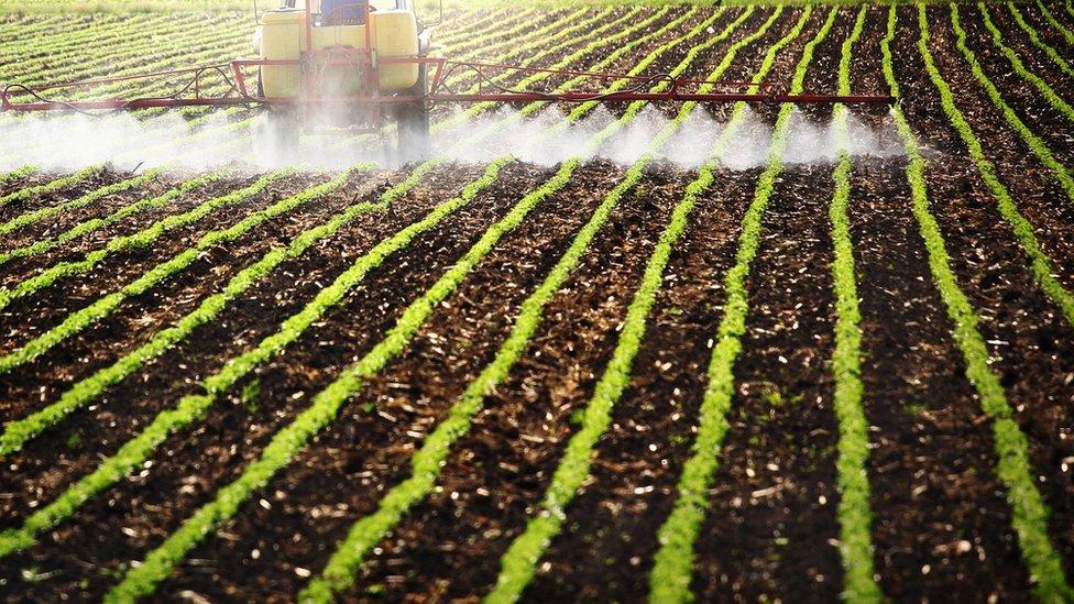 Un tractor con difusores de pesticidas arando un campo de cultivo.
