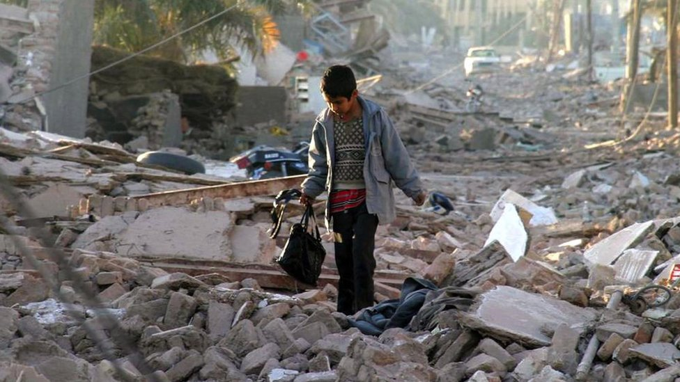 An boy carrying a bag walks on a street where debris is seen after the earthquake in Bam, on 28 December 2003