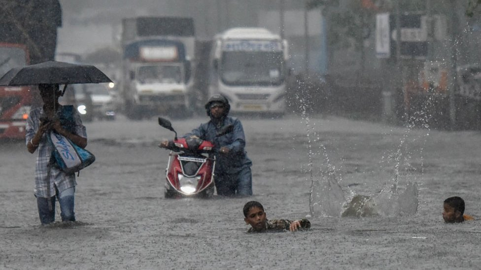 A man pushes a motorbike on a flooded street after heavy rain showers at Santacruz Chembur Link Road, on July 2, 2019 in Mumbai, India.
