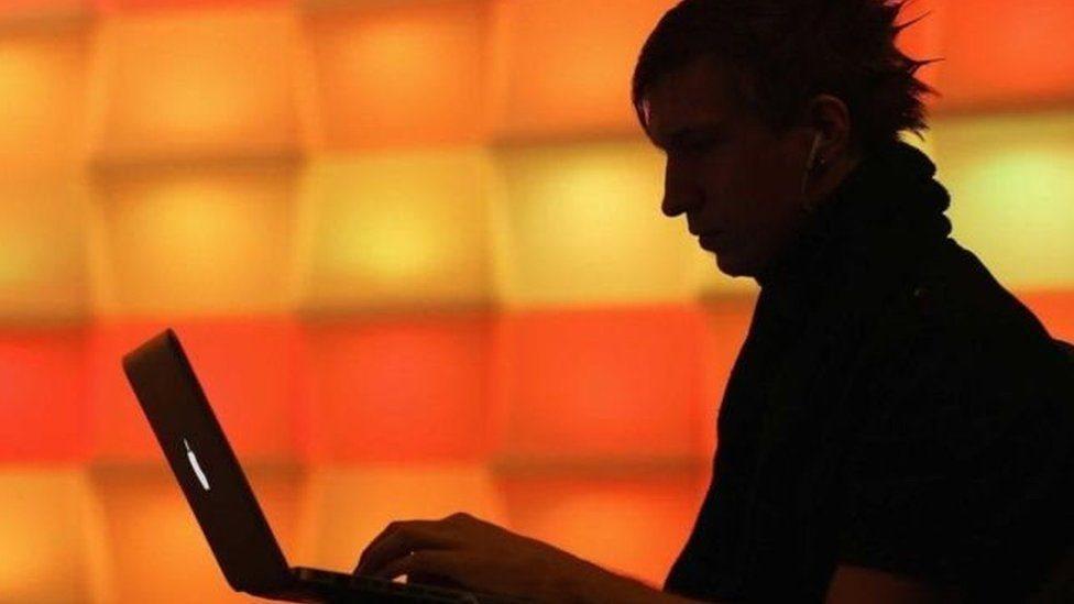 Joven solitario sentado frente a una laptop.