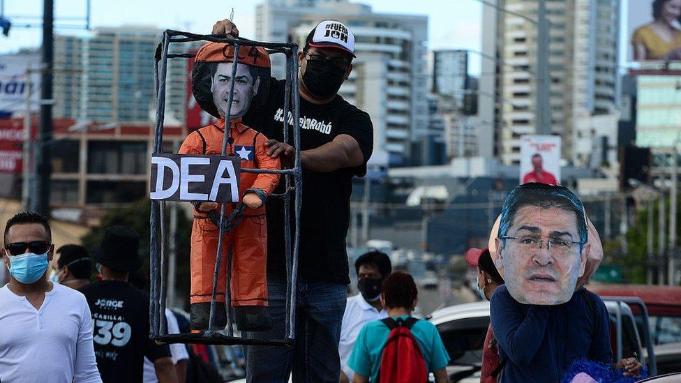 Militantes de la oposiciún muestran una figura con el rostro de Juan Orlando Hernández, tras unos barrotes, junto a un cartel de la DEA.
