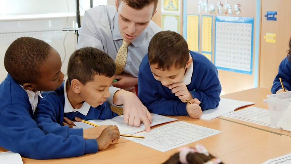 Man teaches three secondary school boys in classroom at their desk with work