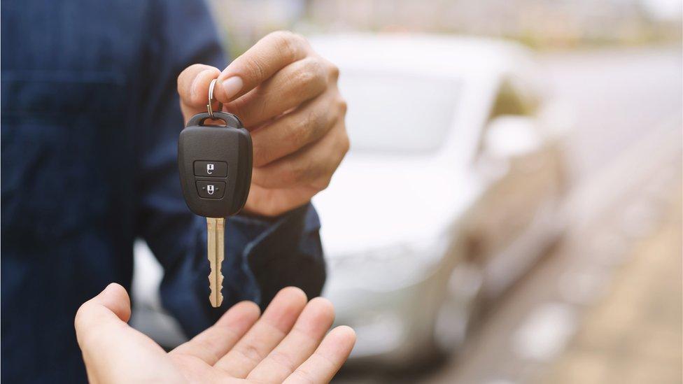 A man handing car keys to a new car owner