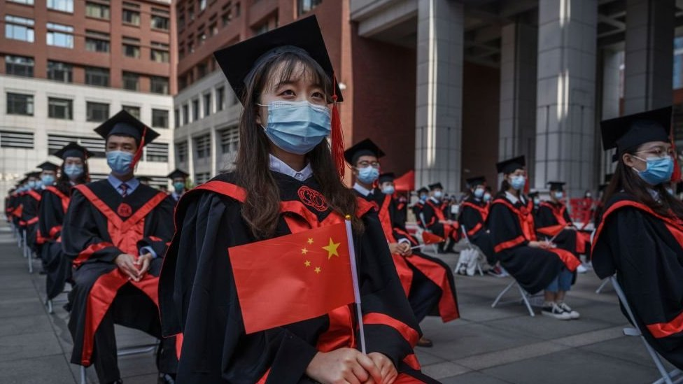 Students wear face masks and hold Chinese flags during a Beijing University open-air graduation ceremony