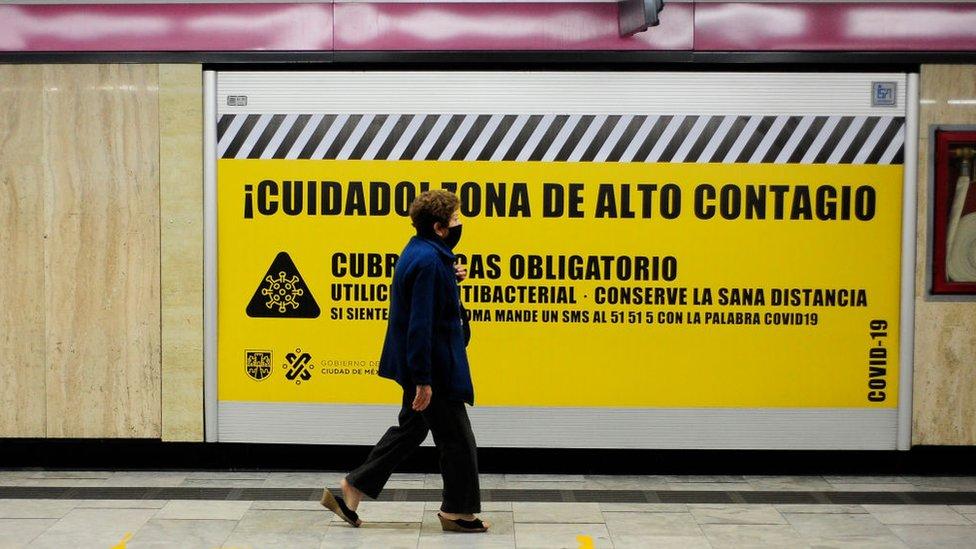 Una mujer con tapabocas pasa frente a un cartel en el metro de la Ciudad de México que aconseja sobre las precauciones contra el coronavirus