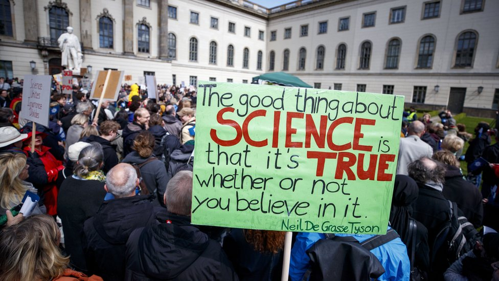 Demonstrators hold banners before the March for Science in front of the Humboldt University in Berlin, Germany, 22 April 2017