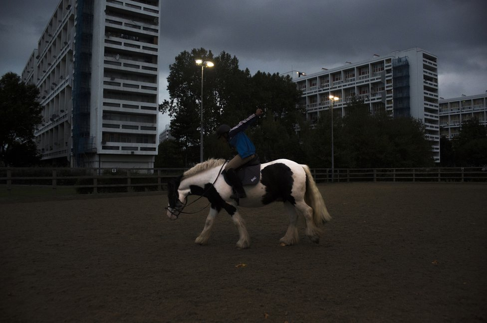 A boy rides a horse against a background of blocks of flats
